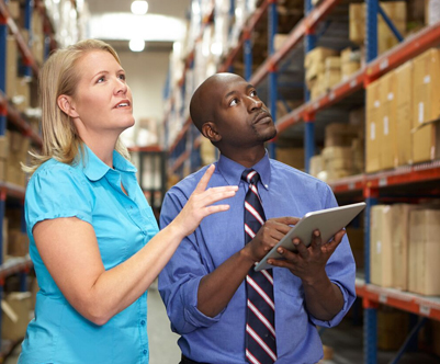 woman and man looking at boxes in the manufacturing/logistics industry